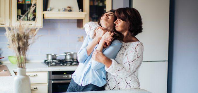 mulher-de-branco-abraça-filha-dias-das-maes
